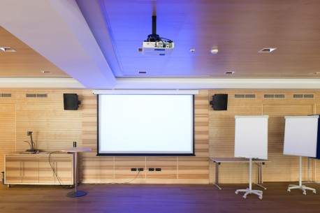 A wall mounted projector screen and two portable projector screens
